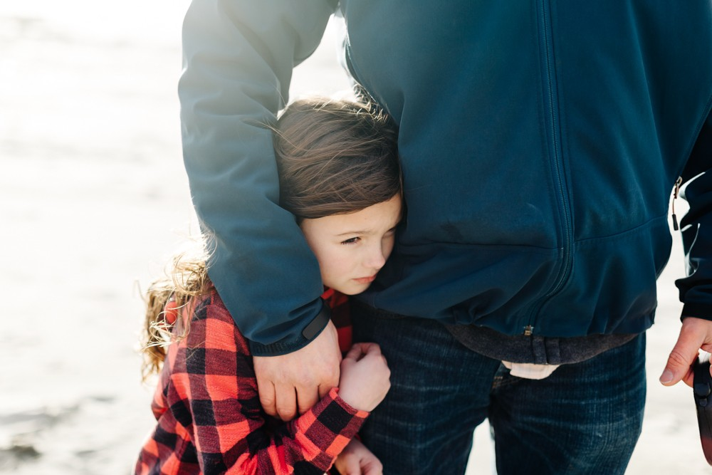 picture of girl hugged by dad on beach by k dimoff photography