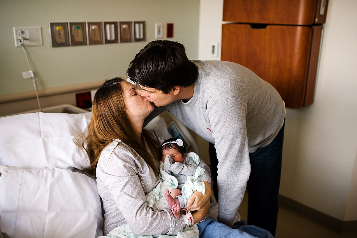 picture of new parents kissing while holding their newborn baby by photographer Bjorna Hoen
