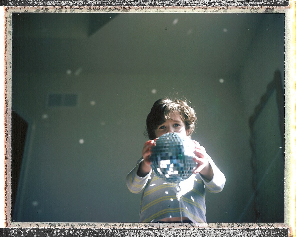 polaroid of little boy with disco ball by kiera eve