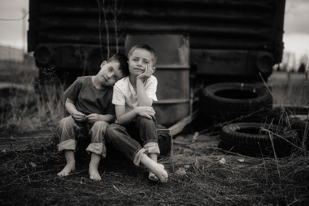 two boys sitting on tires in black and white by photographer steve stanton