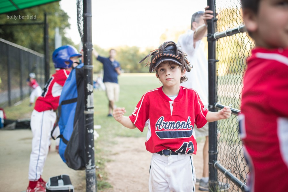 young boy coming into dug out with glove on his head by holly berfield