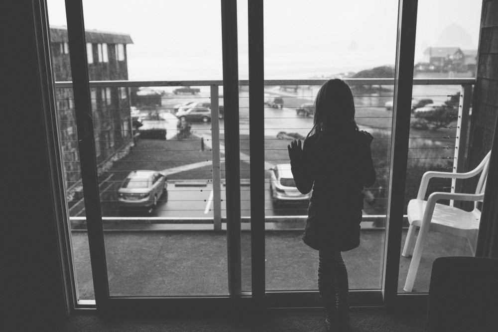 1 picture of girl at hotel room window in cannon beach by photographer shelby brakken