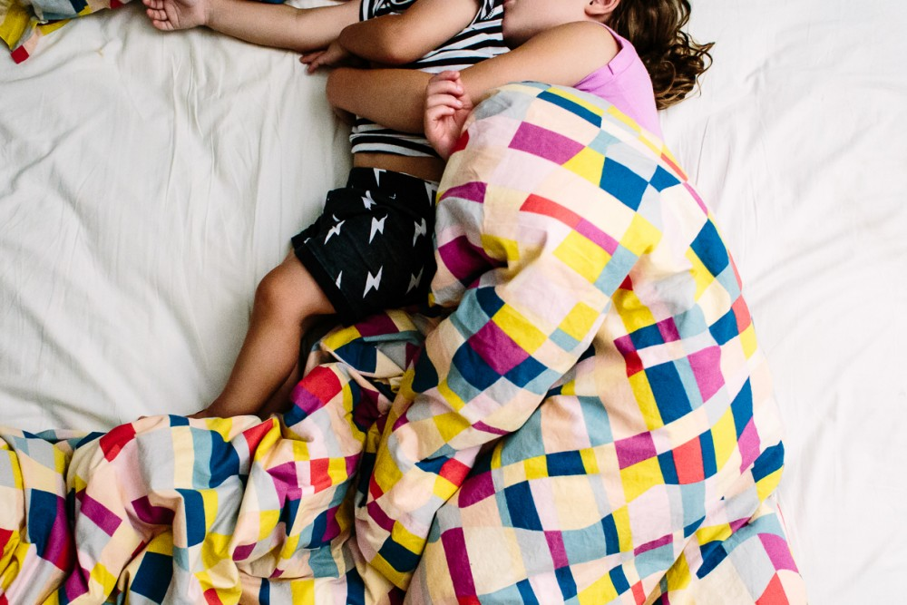 1 picture of two young kids cuddling in bed faceless by natasha kelly