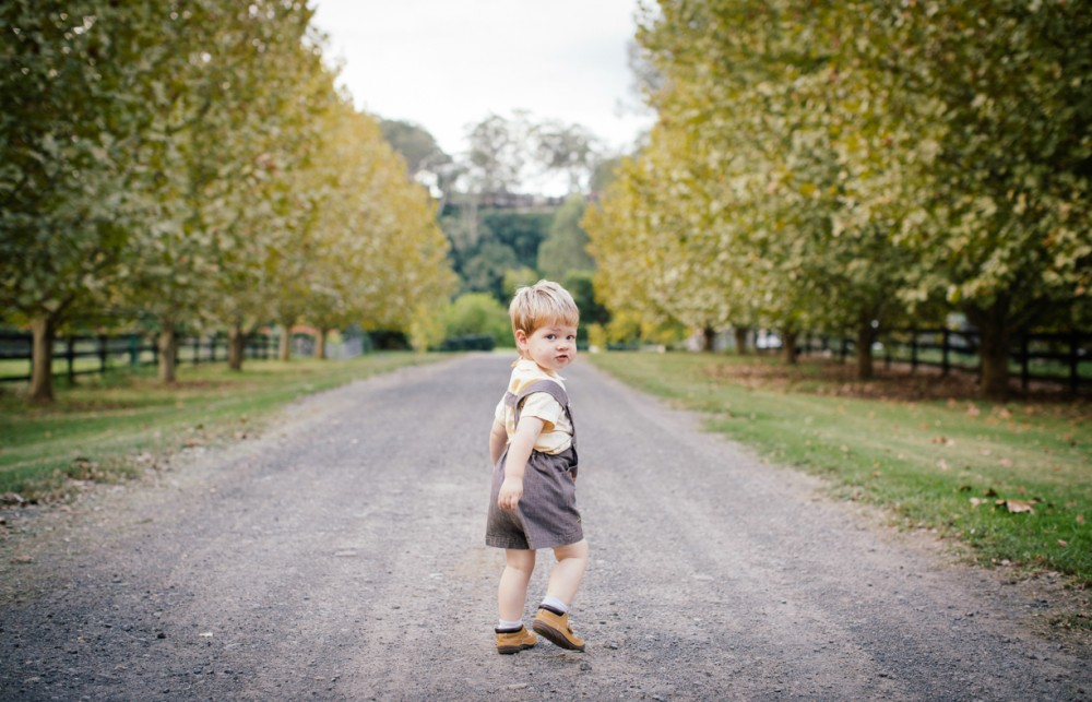 11 picture of young boy walking down dirt road looking back at camera over shoulder by sheridan nilsson