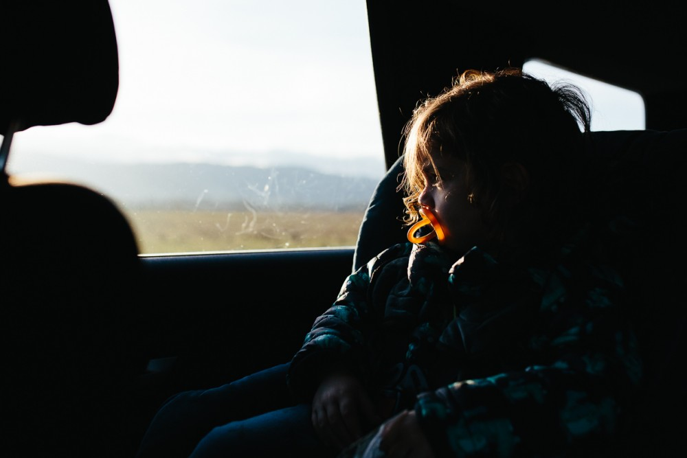 12 photo of child with pacifier binky orange in car looking out window by Natasha Kelly