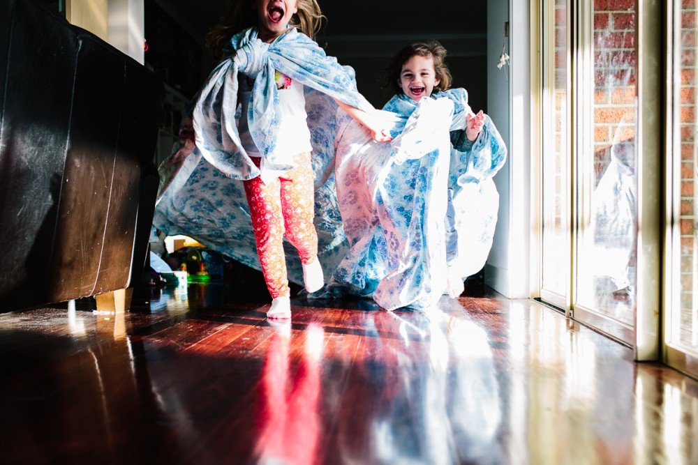 14 image of two young girls running with sheet around neck like cape indoors by Natasha kelly