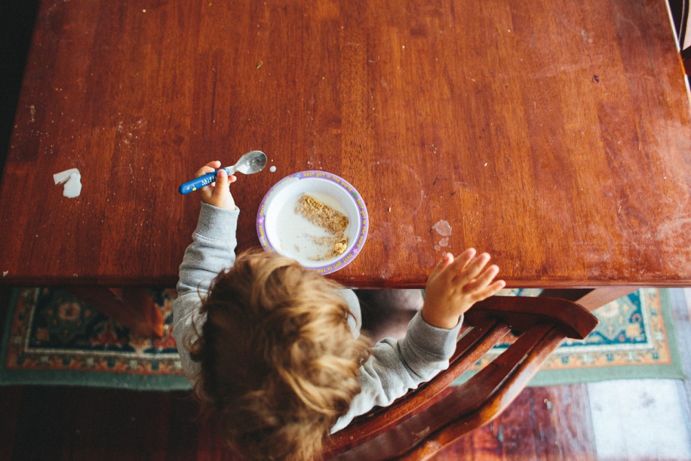 2 image of toddler eating cereal at messy table alone taken from above by Natasha kelly