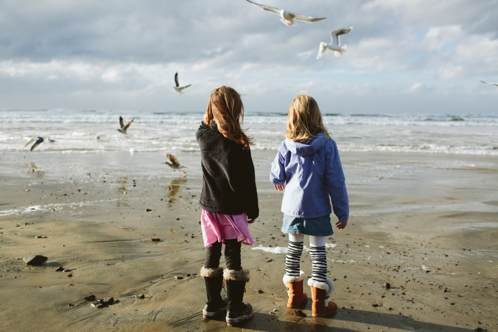 2 picture of girls on Oregon coast beach by photographer shelby brakken