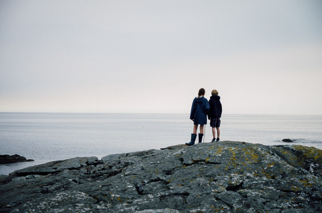 3 Children standing on rocks in Anglesey-NorthWales by photographer Lea Jones