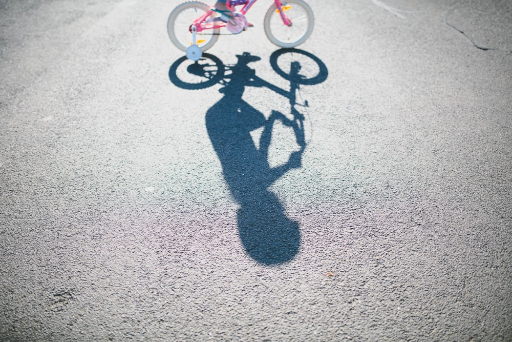 3 photo of young child shadow riding on bike by Natasha kelly