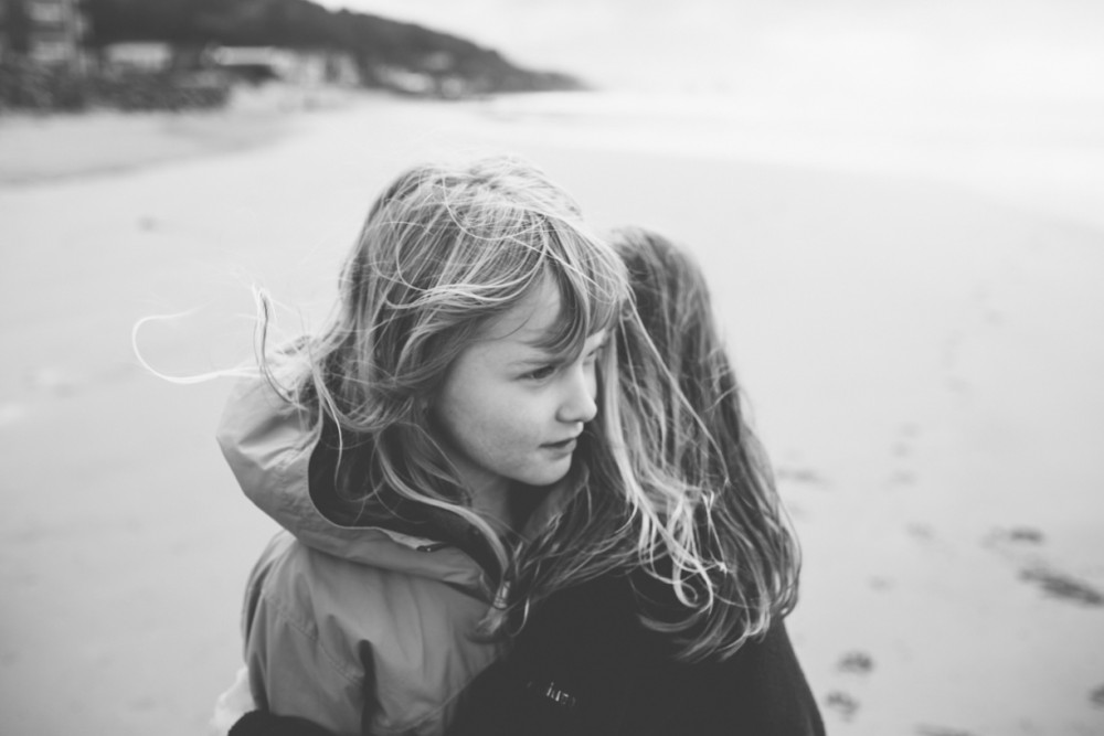 4 Two girls hug on cannon beach by photographer Shelby Brakken