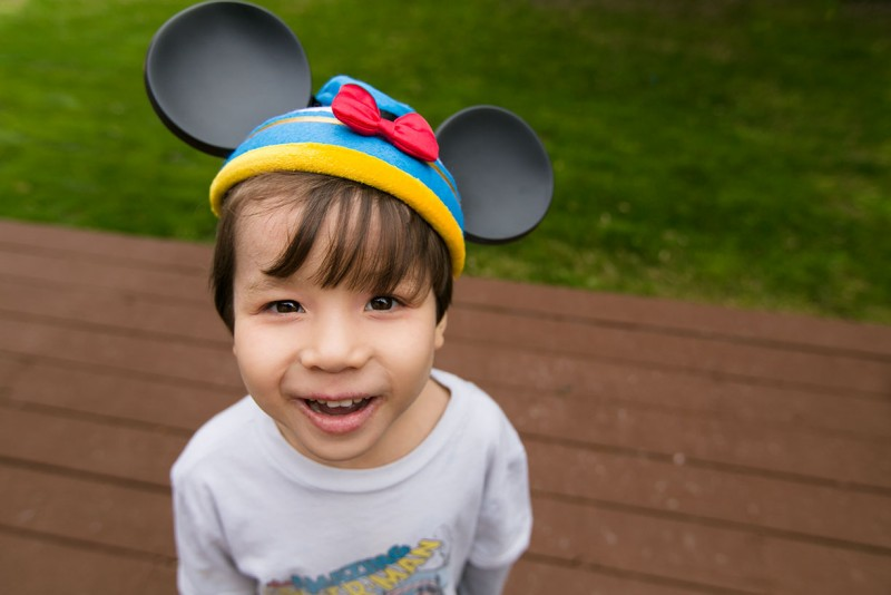 4 young boy with mouse ears hat smiling at camera by heather chang