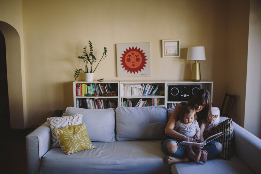 4 young mother reads to toddler daughter on couch in San Francisco house by Rachelle Derouin 5