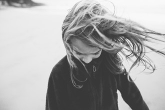 5 girl with wind in hair on cannon beach by photographer shelby brakken