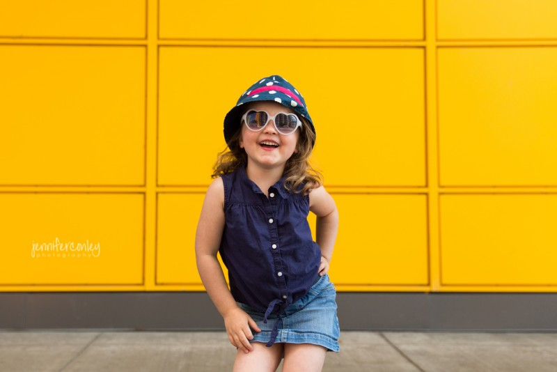 5 picture of young girl in front of yellow wall with heart sunglasses by jennifer conley