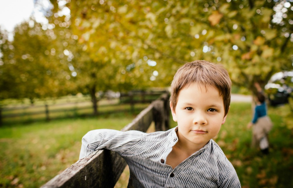 7 photo of young boy hanging on fence autumn by sheridan nilsson