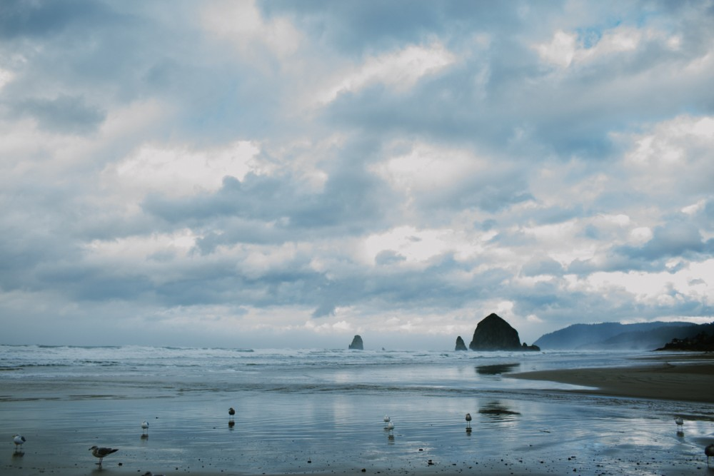 7 picture of cannon beach with reflections and stormy sky by photographer shelby brakken
