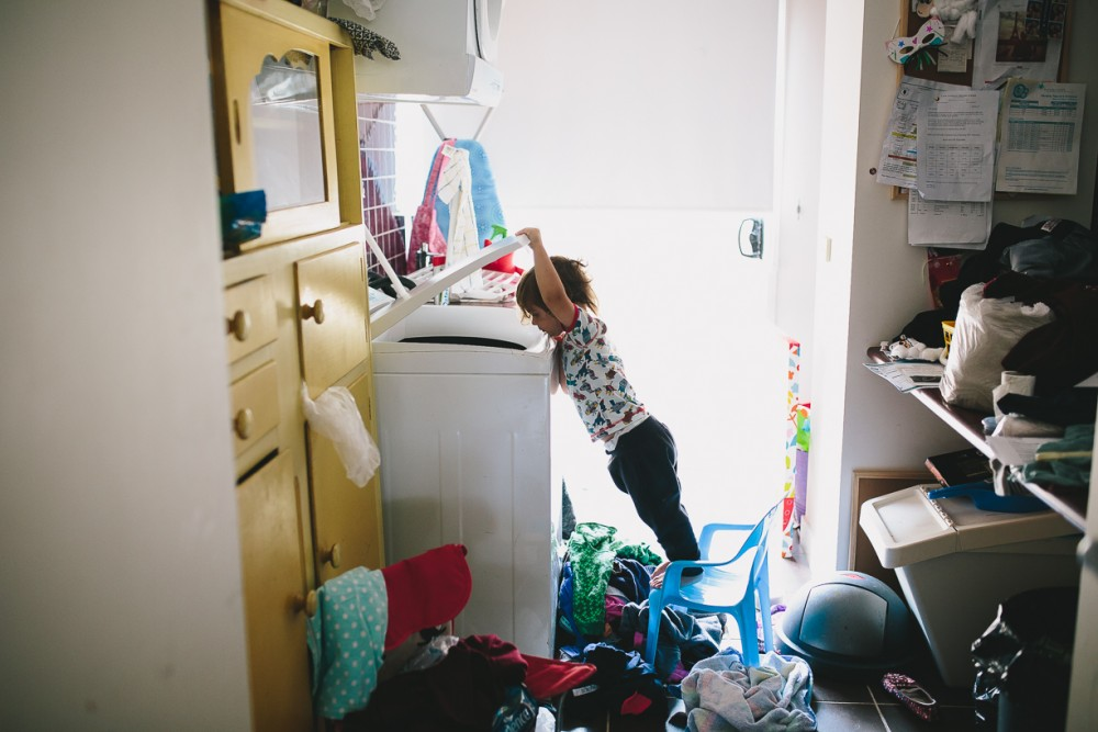 7 picture of young child looking into washer standing on plastic chair by natasha Kelly