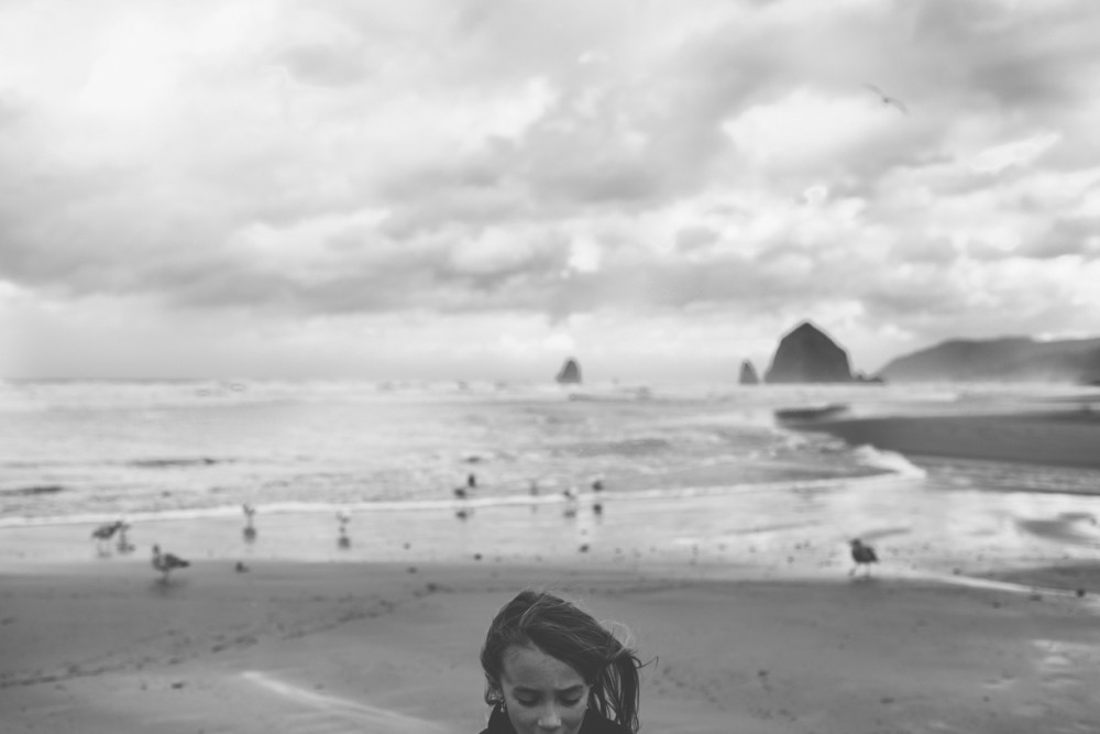 8 girl on stormy cannon beach by photographer shelby brakken