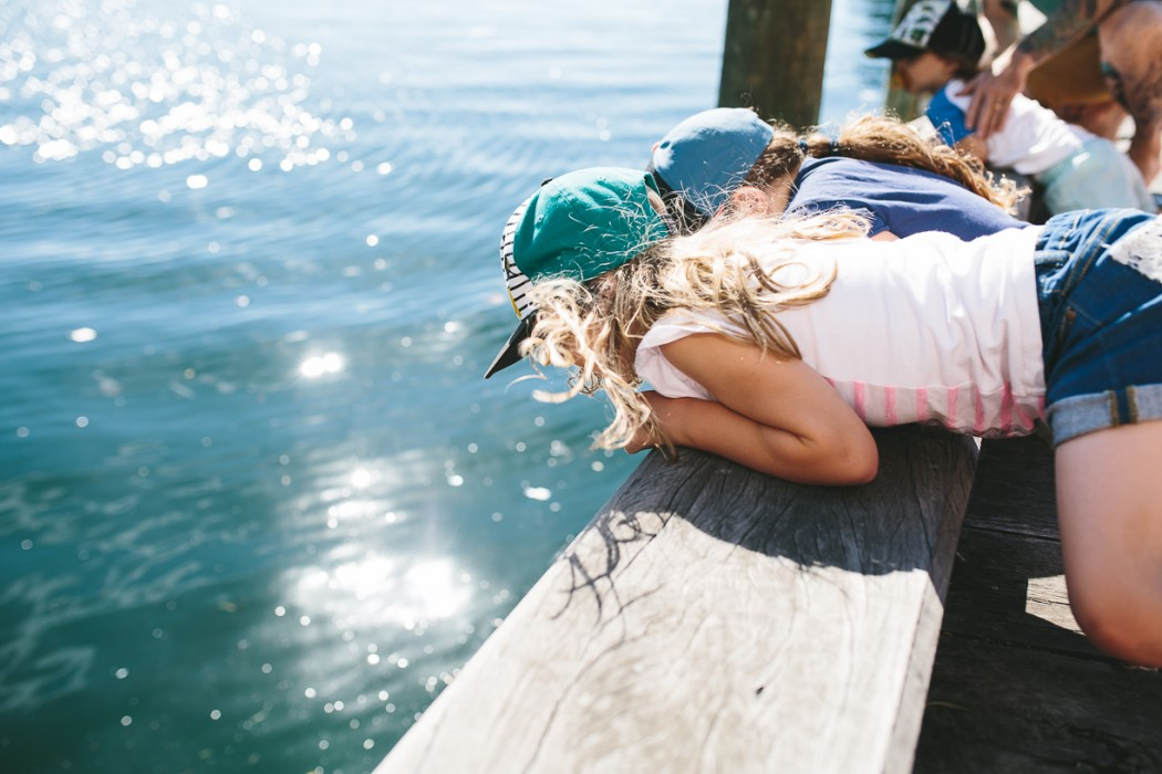 8 image of kids lying on pier looking into water by Natasha kelly