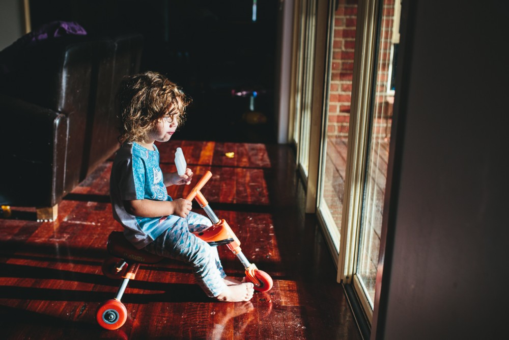 9 photo of child on tricycle eating popsicle inside looking outside glass door by Natasha Kelly