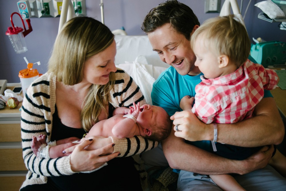 a picture of a new family enjoying their newborn baby by Phoenix photographer Pamela Nicole
