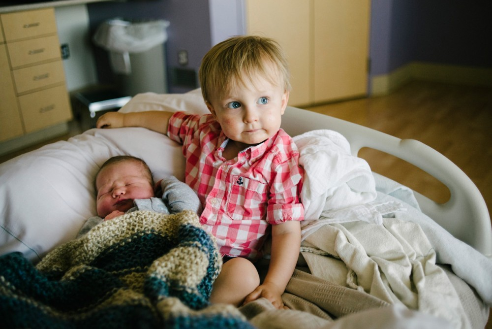 a picture of big brother meeting baby brother for the first time by photographer pamela nicole