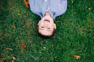 little boy laughing laying on the ground in blue checked shirt by photographer nicki sebastian