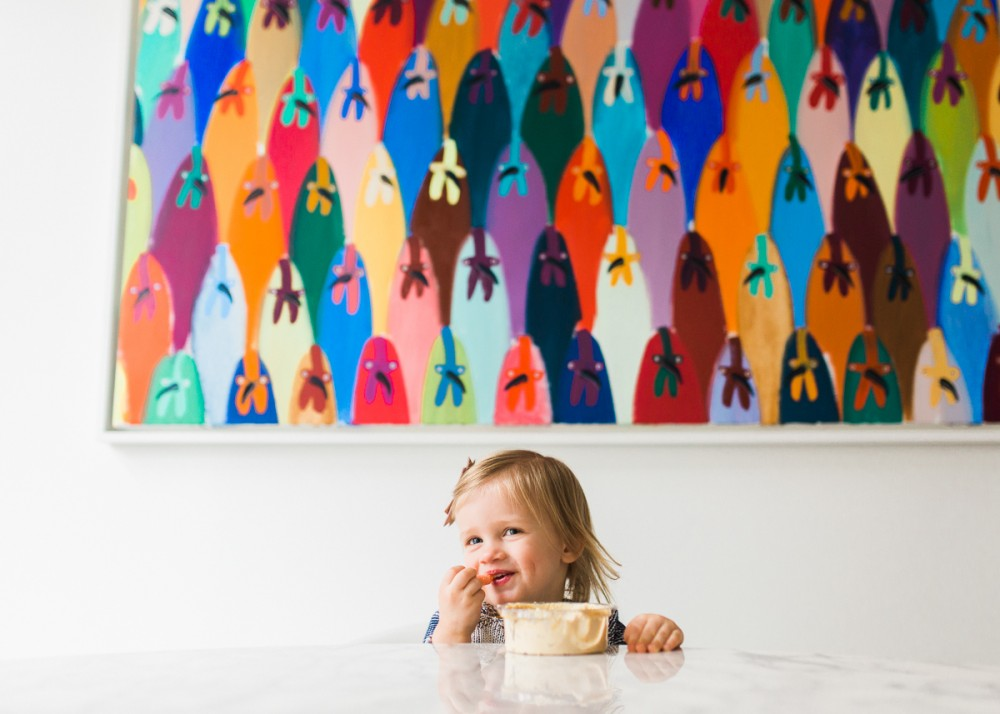 little girl eating at table under huge colorful artwork by photographer nicki sebastian