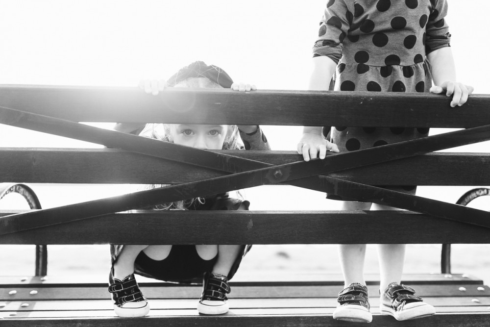 little girl peaking through railing in black and white image by photographer nicki sebastian
