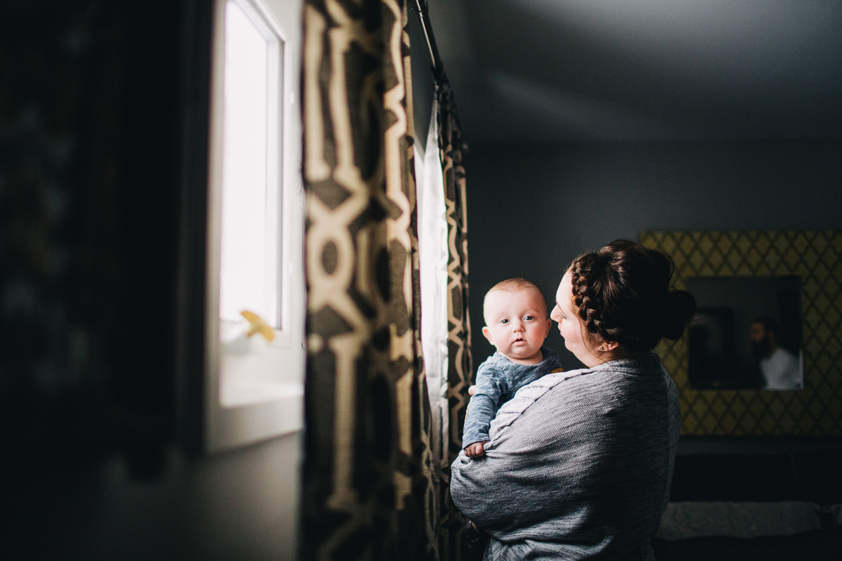 photo of a mom holding her new baby by window light by Parikha Meta