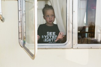 11 girl peeks out of camper by texas photographer brooke schwab