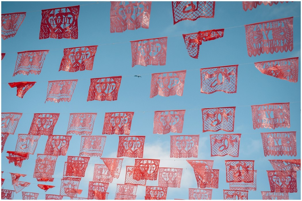 5 Red banners on blue sky in Mexico by photographer Danielle Hatcher