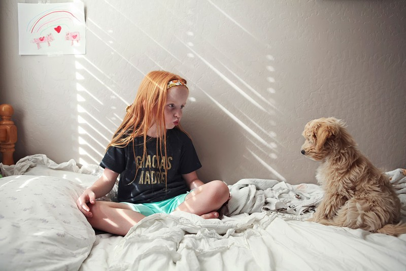 picture of a red haired girl on bed with furry puppy making faces by Joanna Polling