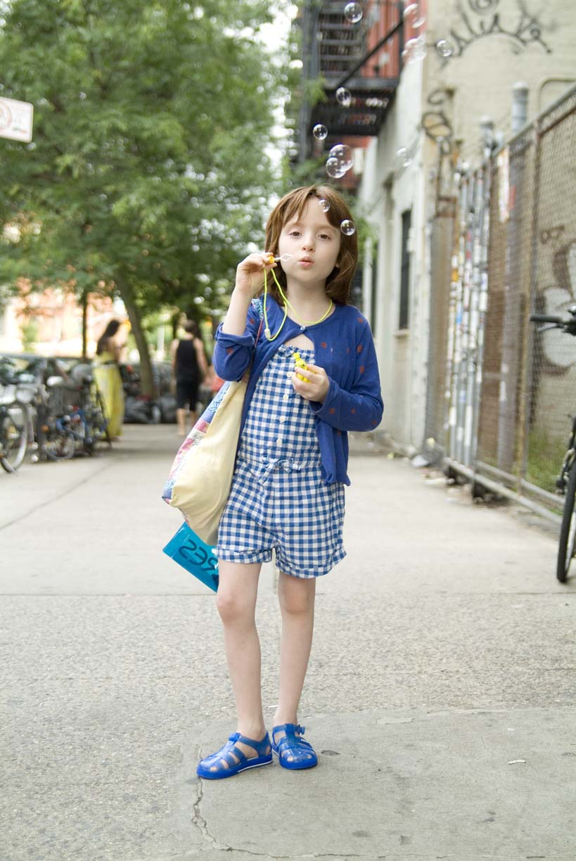 Picture of little girl blowing bubbles on the street by Erica Tashiro