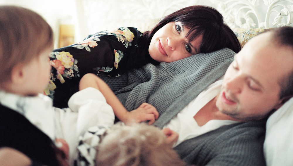 film-image-of-mom-laying-on-dad-with-kids-at-home-by-rebecca-siewert