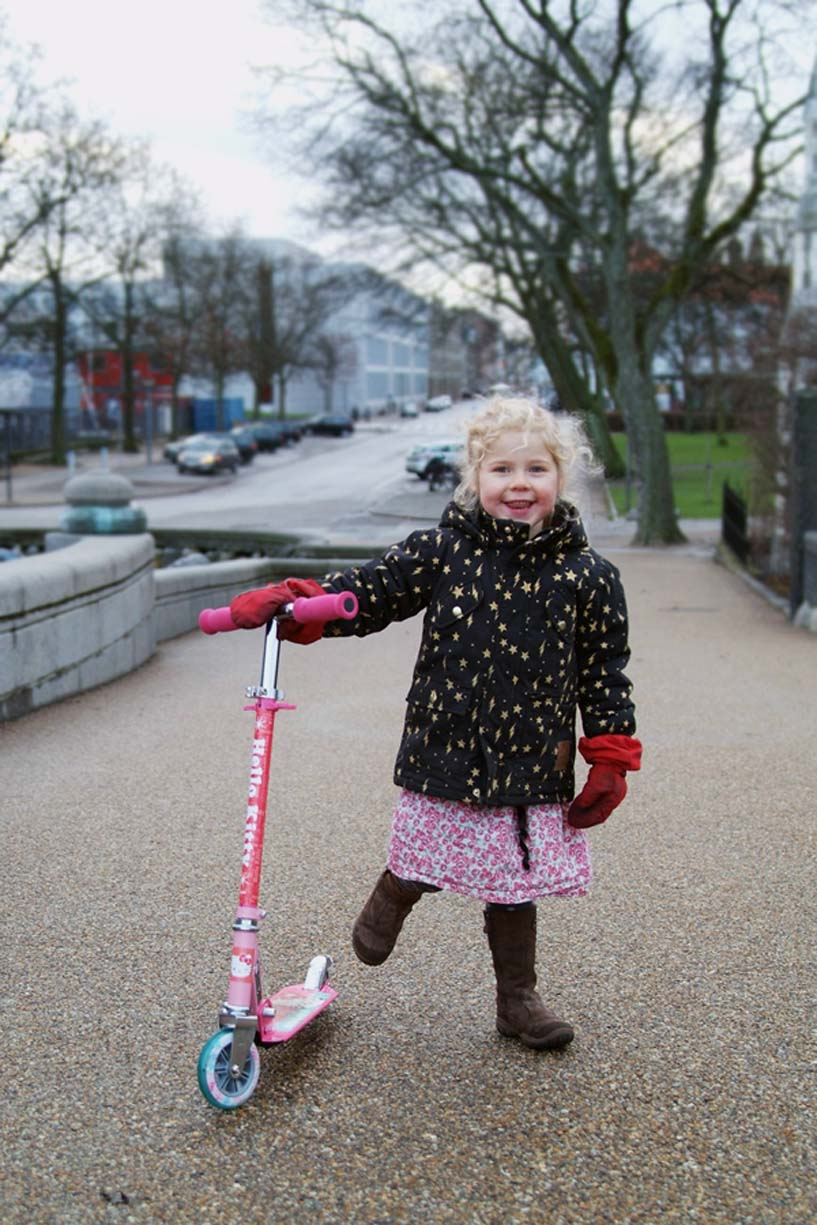 photo of girl dressed for winter with scooter by Erica Tashiro
