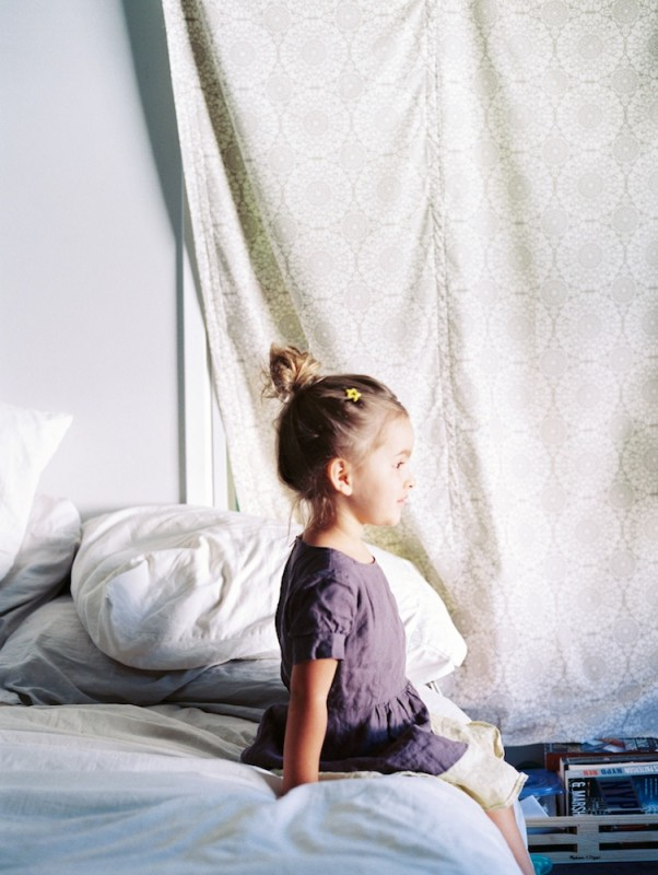 photographer rebecca siewert's film image of little girl on bed with bun in hair and flower