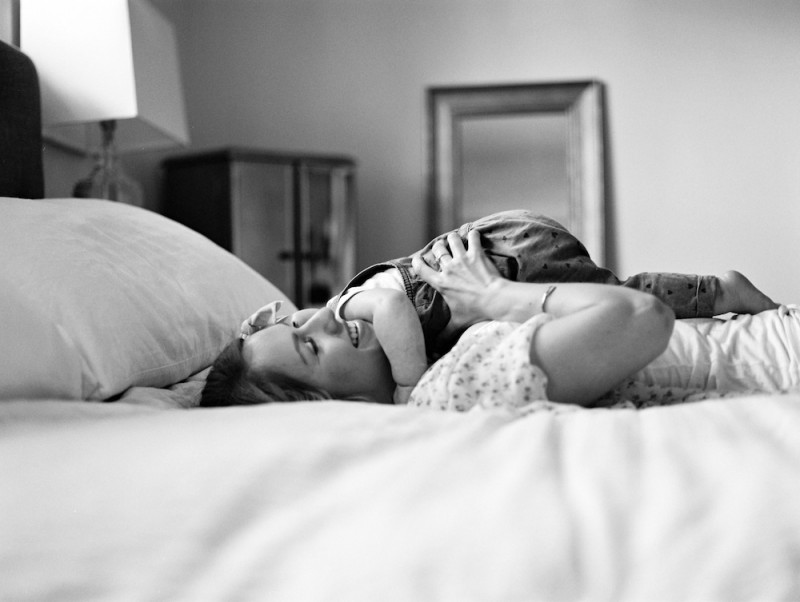 photographer rebecca siewert's film image of mom holding baby laying and smiling on bed