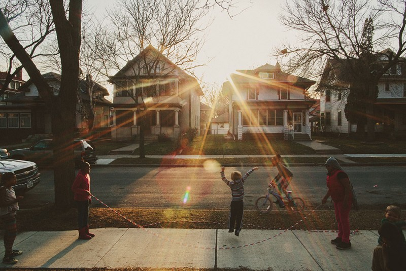 picture of boys playing in street with sun shining down by photographer sarah swanson