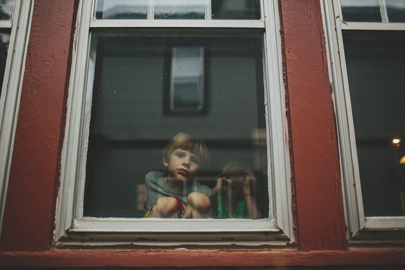photo of boy in window of red house