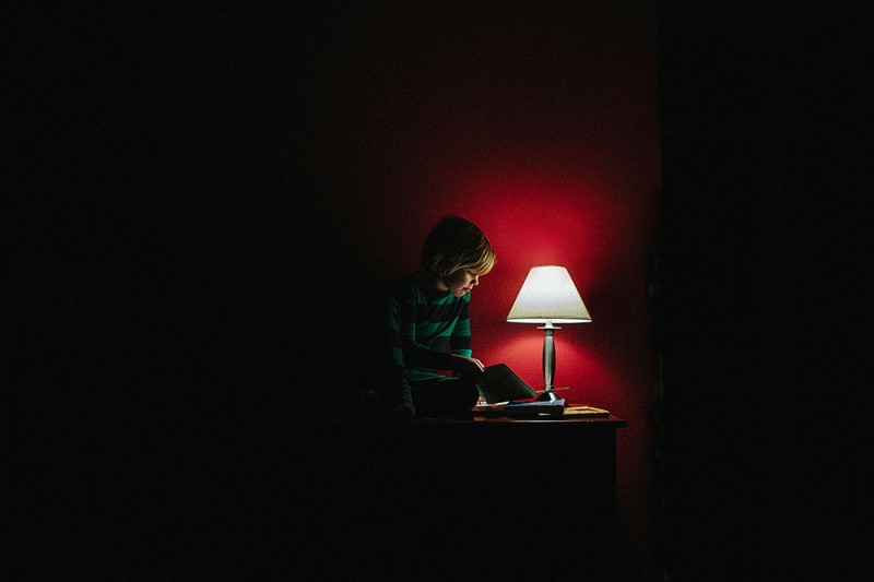 image of boy light up by lamp against red wall by photographer sarah swanson