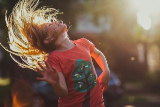 picture of girl flipping her hair in extreme back light by sarah swanson
