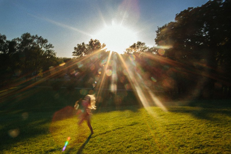 photographepicture of girl running across lawn with sun streaking and shining by photographer sarah swanson