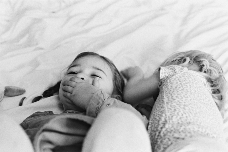 rebecca siewert's black and white film image of little girls laughing on bed