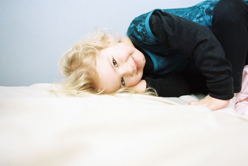 rebecca siewert's film image of little blonde girl with head on bed smiling