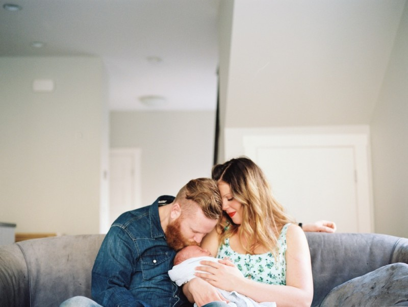 rebecca siewert's film image of pretty mom and dad and baby on living room couch