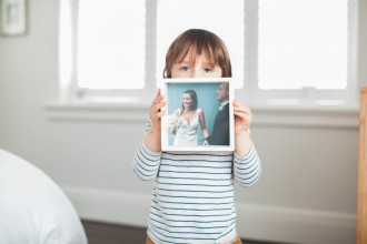 image of young son holding wedding image of his parents by clarissa wikeepa