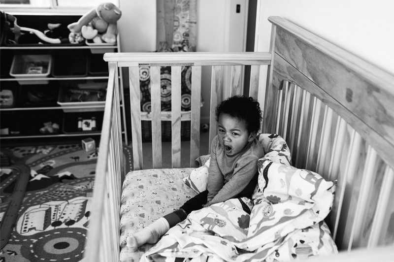 photo of young boy yawning waking up in crib by Carolyn Brandt.jpg