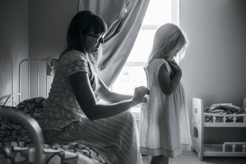photo of mother zipping dressing daughter in white dress by Amanda Voelker